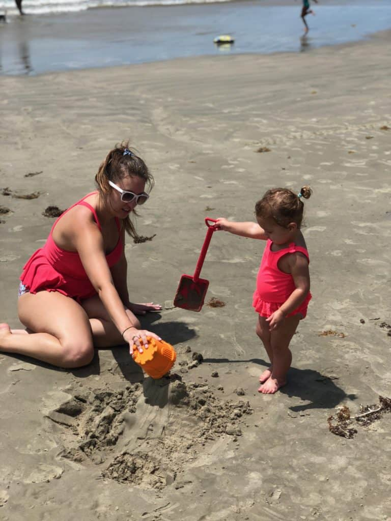 Family Summer Bucket List - mom and daughter building sandcastles at the beach